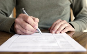 Man writing on paper with pen on table.  Horizontally framed shot.
